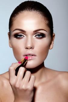 Retrato de primer plano de glamour de hermosa morena sexy caucásica joven modelo aplicando maquillaje lápiz labial en sus labios con piel limpia perfecta