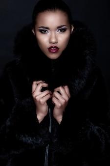 Retrato de primer plano de glamour de hermosa sexy modelo de mujer joven negro con maquillaje brillante con limpieza perfecta con labios rojos en abrigo de pieles