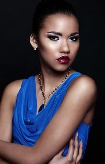 Retrato de primer plano de glamour de hermosa sexy modelo negro joven elegante mujer en vestido azul con accesorios con maquillaje brillante con piel limpia perfecta