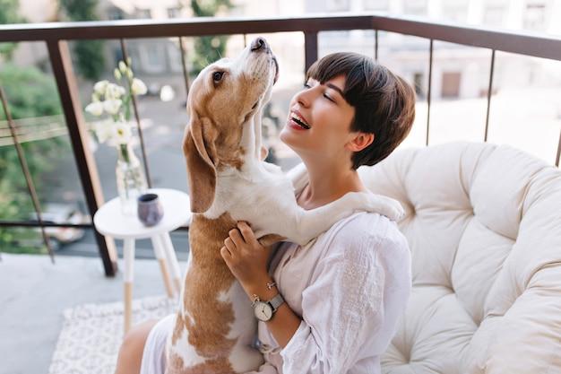 Retrato de primer plano de la hermosa dama de pelo negro mirando con una sonrisa al perrito gracioso mientras está sentado en el balcón. impresionante chica en bata de baño lleva pulsera y reloj de pulsera jugando con perro beagle