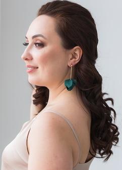 Retrato de primer plano de hermosa mujer joven con peinado elegante y joyas de lujo y