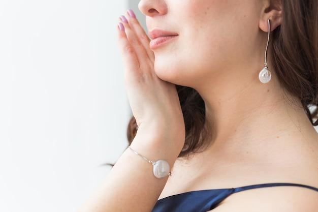Retrato de primer plano de hermosa mujer joven con peinado elegante y joyas de lujo
