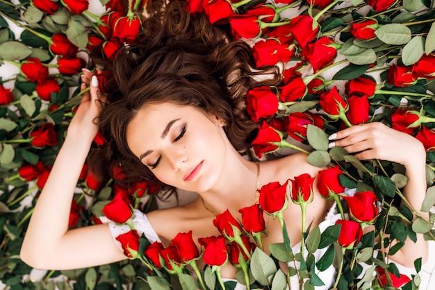 Retrato de primer plano de una hermosa mujer morena en rosas. niña miente rodeada de rosas rojas. maquillaje profesional. concepto de salón de belleza y perfumería