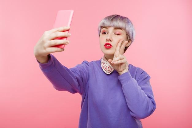 Retrato de primer plano de hermosa niña dollish con cabello corto violeta claro con suéter lila haciendo selfie sobre pared rosa