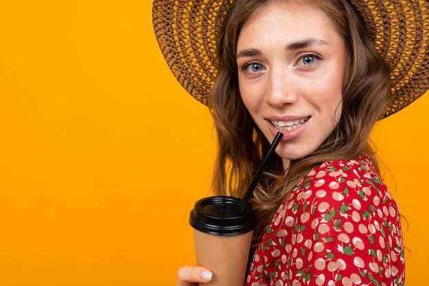 Retrato de primer plano de una hermosa niña de mediana edad con un sombrero sobre un fondo de una pared naranja