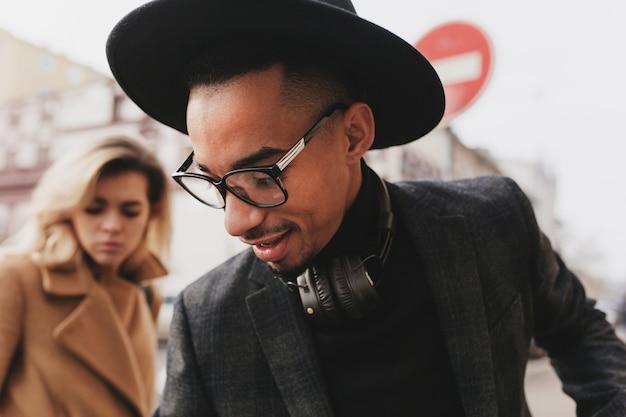 Retrato de primer plano de hombre africano mirando hacia abajo mientras posa con una mujer rubia. modelo masculino negro alegre con sombrero pasar tiempo libre con una chica europea.