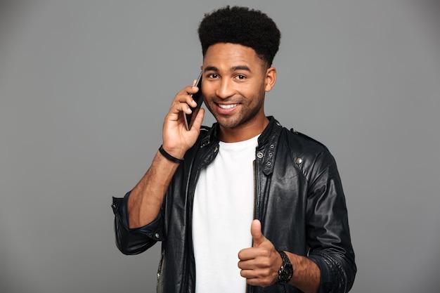 Retrato de primer plano de hombre afroamericano elegante sonriente hablando por teléfono móvil mientras muestra el pulgar hacia arriba gesto, mirando