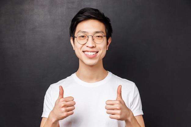 Retrato de primer plano de un hombre joven asiático satisfecho y confiado con una camiseta blanca, mostrar aprobación con el pulgar, sonriendo, garantizar un buen producto, recomendar un servicio o compañía,