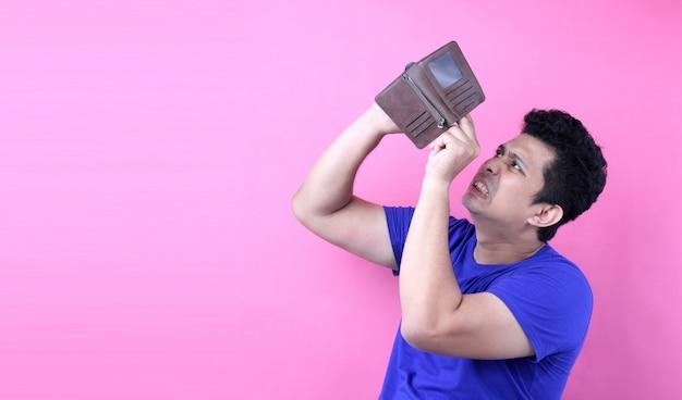 Un retrato de primer plano de un hombre sin palabras sorprendido, sorprendido asia, sosteniendo una billetera vacía sobre fondo rosa en studio