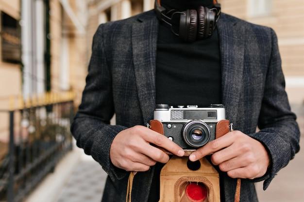 Retrato de primer plano de hombre viste camisa negra y chaqueta gris posando en la calle por la mañana. foto de fotógrafo con cámara de sujeción de piel marrón claro.