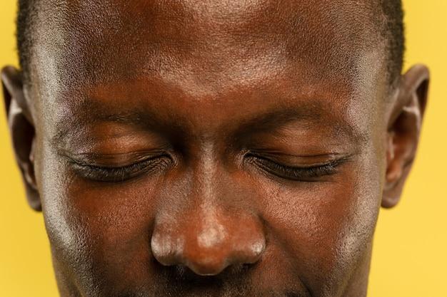 Retrato de primer plano del joven afroamericano sobre fondo amarillo de estudio. precioso modelo masculino con piel cuidada. concepto de emociones humanas, expresión facial, ventas, publicidad. ojos y mejillas.