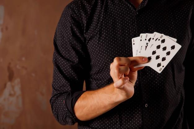 Retrato de primer plano de joven con cartas de juego. chico guapo muestra trucos con tarjeta. manos hábiles de magicia