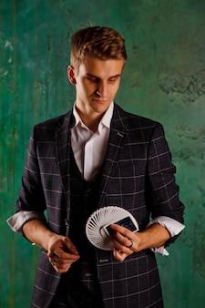 Retrato de primer plano de joven con cartas de juego. chico guapo muestra trucos con tarjeta. manos inteligentes de mago