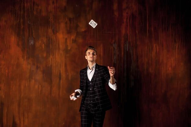 Retrato de primer plano de joven con cartas de juego. chico guapo vomita con tarjeta. manos inteligentes de mago
