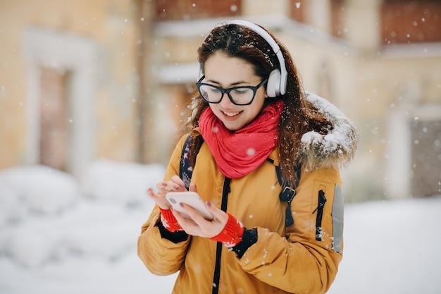 Retrato de primer plano joven en la ciudad de invierno, sonriendo