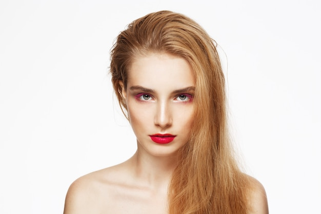 Retrato de primer plano de joven hermosa chica segura con maquillaje brillante. pared blanca. aislado.