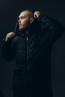 Retrato de primer plano de un joven serio en una chaqueta mirando hacia el lado en un espacio gris. calvo con barba