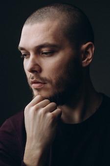 Retrato de primer plano de un joven serio mirando a otro lado en un espacio gris. calvo con barba