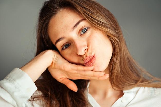 Retrato de primer plano de una joven sonriente en una camisa blanca en una pared gris. de buen humor. sin retoques y maquillaje.