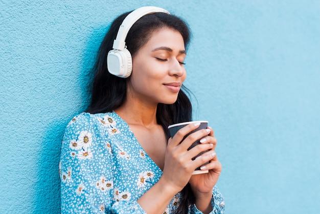 Retrato de primer plano de lado mujer sosteniendo un café