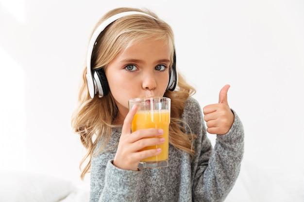 Retrato de primer plano de linda chica en auriculares bebiendo jugo de naranja, mostrando el pulgar hacia arriba gesto
