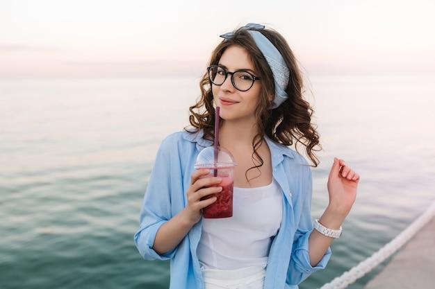 Retrato de primer plano de una linda chica inspirada en gafas disfruta de la brisa del mar temprano en la mañana