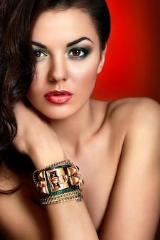 Retrato de primer plano de look.glamor de alta moda de hermosa modelo de mujer joven caucásica sexy con labios rojos, maquillaje verde brillante, con piel limpia perfecta con joyas en mano aisladas sobre fondo rojo