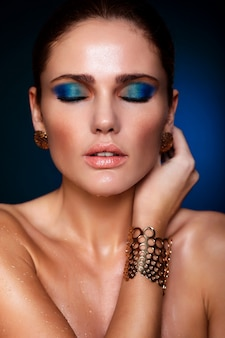 Retrato de primer plano de look.glamor de alta moda de hermosa modelo sexy de mujer joven de raza blanca con labios jugosos, maquillaje azul brillante, con piel limpia perfecta con ojos cerrados