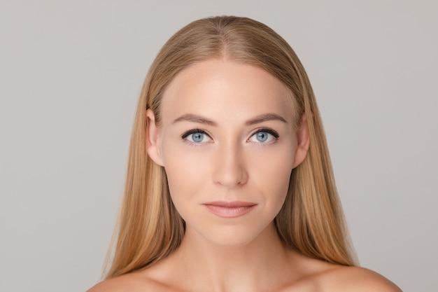 Retrato de primer plano medio de hermosa joven europea aislada en estudio blanco backgroundaving emoción positiva