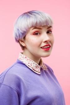 Retrato de primer plano de moda de hermosa niña dollish sonriente con cabello violeta claro corto con suéter lila sobre pared rosa