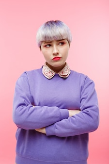 Retrato de primer plano de moda de niña dollish hermosa decepcionada con cabello violeta claro corto con suéter lila sobre pared rosa