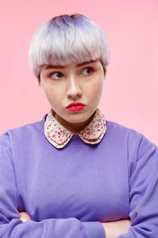 Retrato de primer plano de moda de niña dollish hermosa enojada con cabello violeta claro corto con suéter lila sobre pared rosa