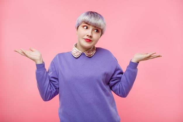 Retrato de primer plano de moda de sorpresa hermosa niña dollish con cabello corto violeta claro con suéter lila sobre pared rosa