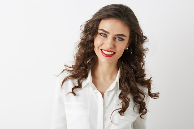 Retrato de primer plano de una mujer atractiva sonriente con dientes blancos, pelo largo y rizado, maquillaje de lápiz labial rojo mirando en cámara aislada con blusa blanca