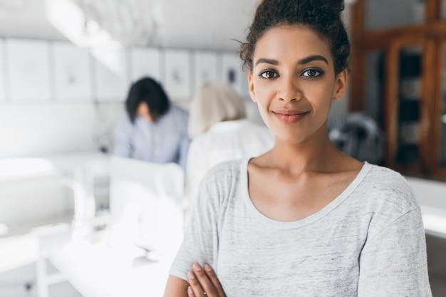 Retrato de primer plano de mujer bonita mulata con maquillaje de moda de pie con los brazos cruzados en la oficina. foto interior de empleada negra posando con colegas internacionales detrás y sonreír suavemente.
