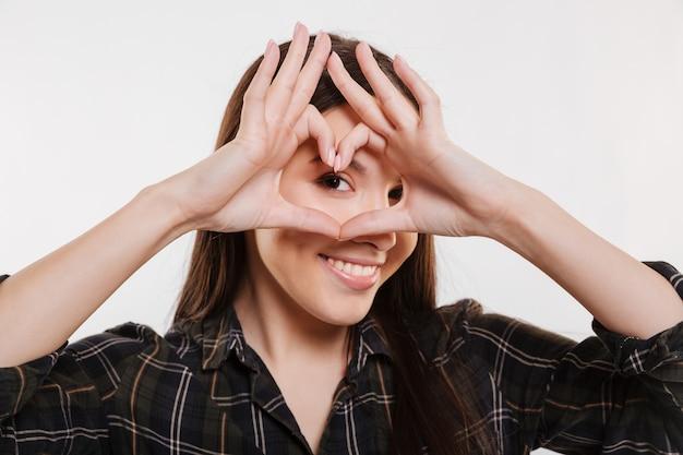 Retrato de primer plano de mujer en camisa mostrando el signo del corazón