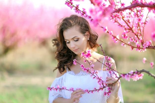 Retrato de primer plano de mujer cerca de palo de rosa floreciente