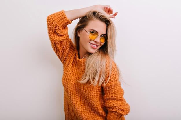 Retrato de primer plano de mujer dichosa en gafas de sol redondas de moda posando en suéter naranja nuevo