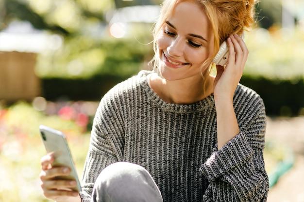 Retrato de primer plano de mujer escuchando música de buen humor, vestida con suéter de punto gris.