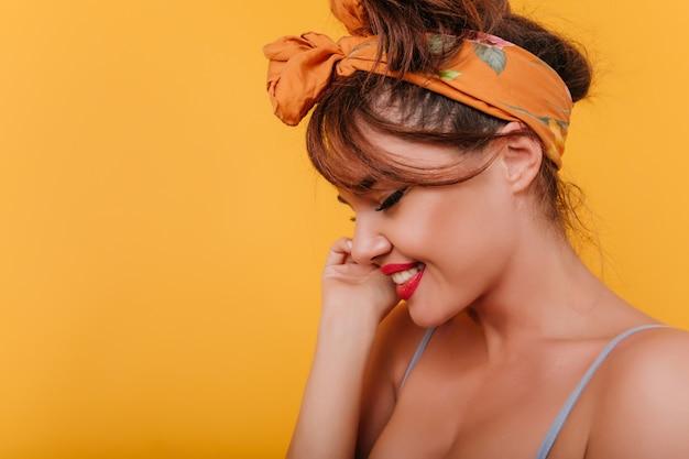 Retrato de primer plano de mujer europea con piel bronceada posando con sonrisa tímida