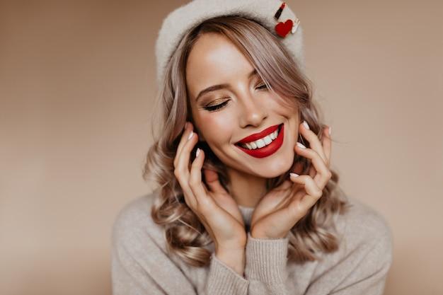 Retrato de primer plano de la mujer francesa rubia feliz con labios rojos