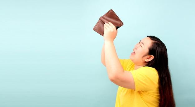 Un retrato de primer plano de una mujer sin habla sorprendida, sorprendida asia, sosteniendo una billetera vacía sobre fondo azul en studio
