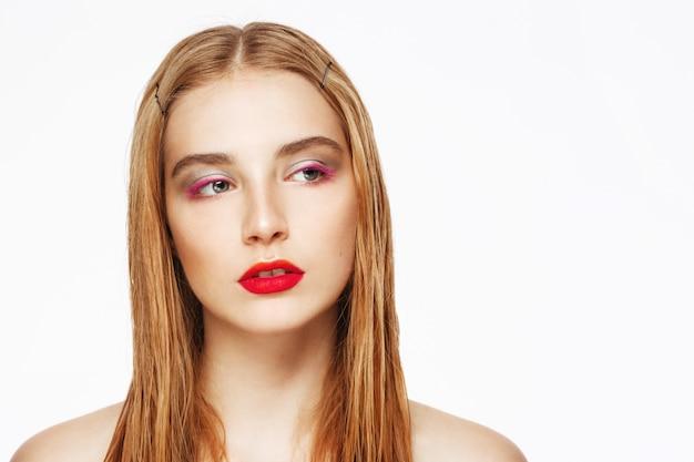Retrato de primer plano de mujer joven confiada con maquillaje brillante.