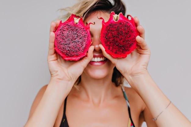 Retrato de primer plano de mujer joven guapa jugando durante la sesión de fotos con frutas de dragón. magnífica chica de pelo corto sosteniendo pitaya roja.