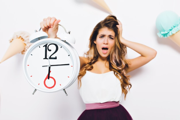 Retrato de primer plano de mujer joven infeliz con cabello largo brillante, tocando su cabeza en pánico. chica desafortunada con ropa de moda sosteniendo un gran reloj llega tarde al trabajo y grita.