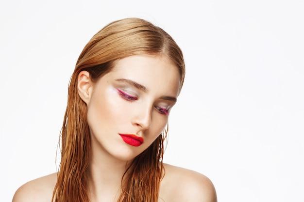 Retrato de primer plano de mujer joven con maquillaje brillante.