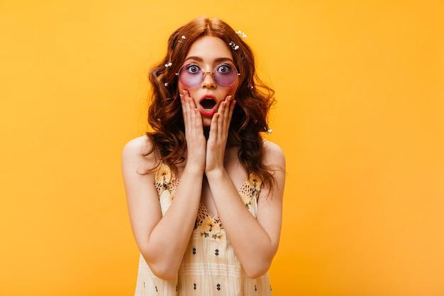 Retrato de primer plano de mujer pelirroja con flores silvestres en el pelo mirando sorprendido a la cámara. mujer con gafas de color lila posando sobre fondo aislado.