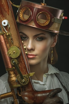 Retrato de primer plano de mujer steampunk con una pistola en la mano.