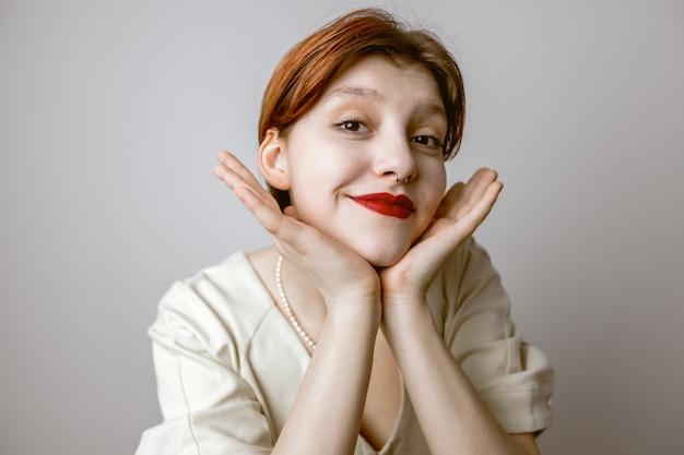 Retrato de primer plano de mujeres con labios rojos tocando la cara y sonriendo
