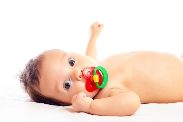 Retrato de primer plano de una niña bonita curiosa acostada en un diván y jugando con un sonajero sobre un fondo blanco. el concepto de desarrollo y cuidado de los bebés. copyspace